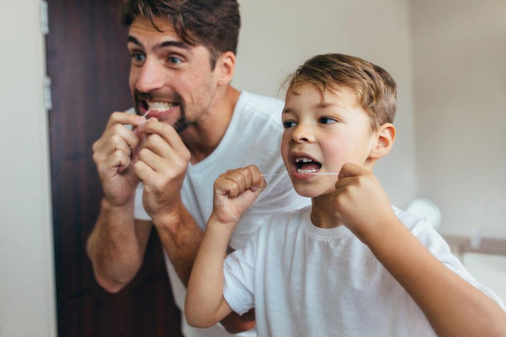 Vater und Sohn putzen sich vor dem Spiegel die Zähne.